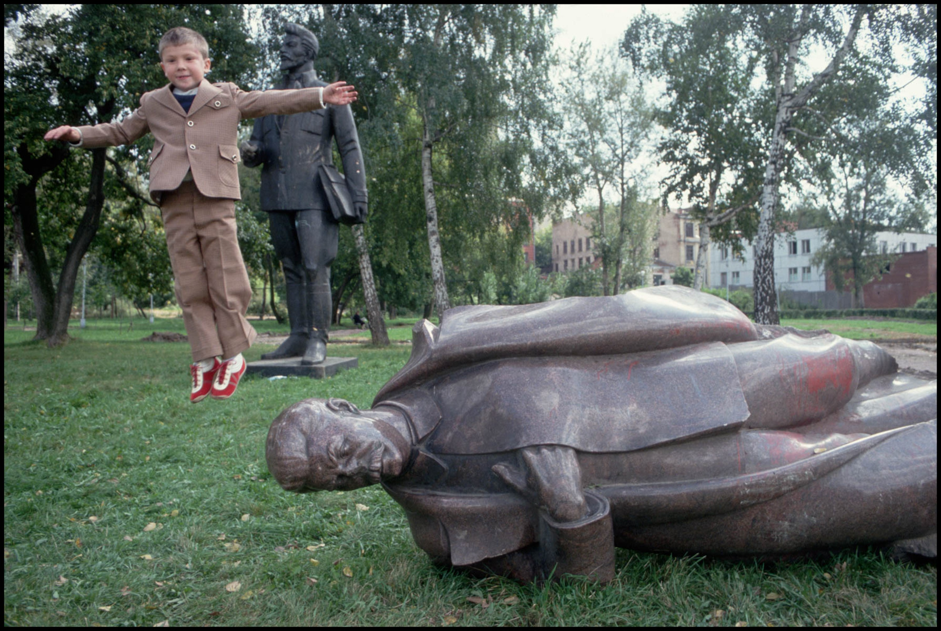 Russian Child jumps off toppled statue of Stalin, 1991 by Peter Turnley