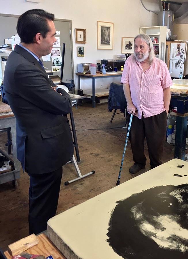 A behinds the scenes photo from the film A Story In Stone. Eric Mourlot (left), the grandson of French lithographer Ferdinand Mourlot, discusses the history and process of lithography with James Reed.